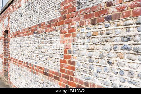 Old flint and brick wall in the UK. - Stock Image
