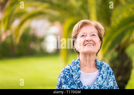 Portrait of happy cheerful caucasian senior lady smiling and looking upside - outdoor nature green tropical background - blue shirt and blonde hair - Stock Image
