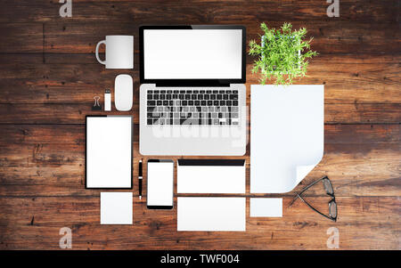 top view of wooden desktop with devices, branding elements and office stuff 3d rendering mockup - Stock Image