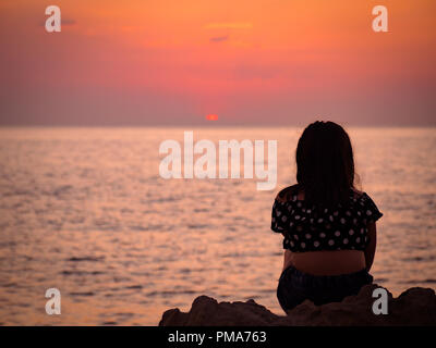 A young giel watches the sunset over San Antonio bay, Ibiza - Stock Image