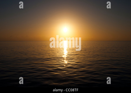 The sun approaches the horizon on a very clear and calm day over the water. Taken at Swains Reef on the southern - Stock Image