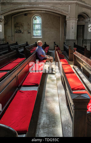 Zionskirche, Zion church interior detail with elderly man sitting on pew,  Mitte-Berlin, Germany - Stock Image