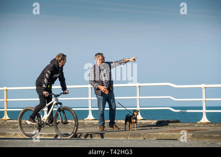 Aberystwyth Wales UK. 13 April 2019. UK Weather: People on the promenade on a  bright snd sunny  April springtime morning with clear blue skies  but  a cold easterly wind blowing  in Aberystwyth on the Cardigan Bay coast of west Wales.