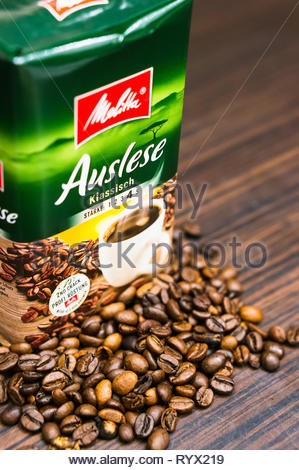 Poznan, Poland - March 12, 2019: Melitta Auslese coffee in a package and fresh roasted beans on a wooden surface in soft focus. - Stock Image