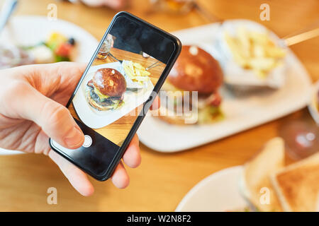 Hamburger Teller is photographed with a smartphone for a food blog - Stock Image