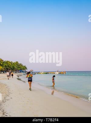 Running on West Bay Beach Roatan Honduras in the early morning. - Stock Image