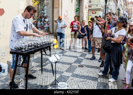 Street performer plays on glasses in front of tourists, Mala Strana, Prague, Czech Republic - Stock Image