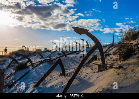 Tourist woman at Cemetery of Anchors. Memorial monument to dead fishermen of tuna industry in Portugal. Baril beach, Santa Luzia, Algarve - Stock Image