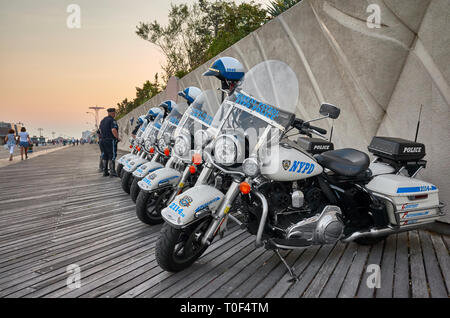 New York, USA - July 02, 2018: NYPD Highway Patrol motorcycles parked on the Coney Island beach boardwalk at sunset. - Stock Image