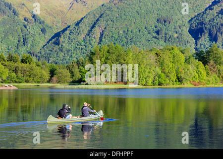 Two men paddling a Canadian canoe across Lake Haukeland in summer near Bergen, Hordaland, Norway, Scandinavia - Stock Image