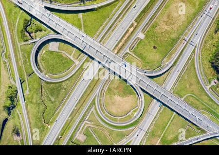 Big road junction on green land aerial view. Highway and half clover leaf junction with traffic - Stock Image