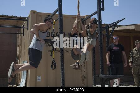 UFC athletes from left, Jake Ellenberger, Diego Sanchez, and Emily Miller, exercise while visiting U.S. Army Paratroopers at Camp Swift, Iraq, June 5, 2017. The athletes participated in the Pro Sports MVP MMA Cage Crusader Tour and visited service members deployed in support of Combined Joint Task Force-Operation Inherent Resolve. CJTF-OIR is the global Coalition to defeat ISIS in Iraq and Syria. - Stock Image