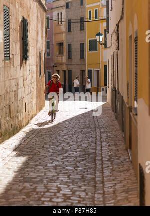 A man cycles through the streets of Ciutadella, Menorca. Balearic Islands - Stock Image
