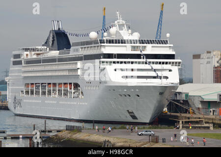 The cruise ship MSC Opera anchored at Southampton docks, the people in the foreground provide a sense of scale. - Stock Image