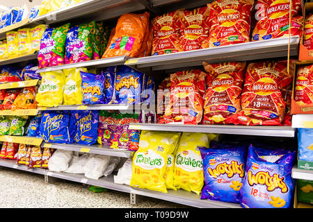 Crisps and snacks for sale in a supermarket, UK. - Stock Image