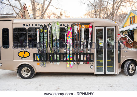 Colorful skis in outside storage rack on Chevrolet shuttle bus that is part of Galloping Goose transit system in Telluride, San Miguel County, Colorad - Stock Image