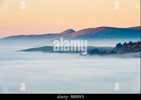 On the Welsh border near Knighton, Powys, UK. Early morning view west from Stonewall Hill showing the valleys filled with thick fog - Stock Image