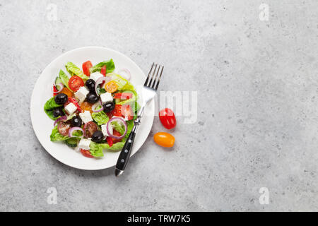 Greek salad with cucumber, tomato, pepper, lettuce, onion, feta cheese and olives, dressed with olive oil. Top view with copy space - Stock Image