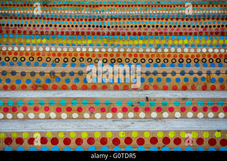 Colorful circles painted on the wooden stairs - Stock Image