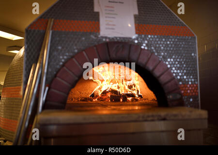 Fire in dome ceramic wood burning pizza oven at Amsterdam Brewhouse Toronto - Stock Image
