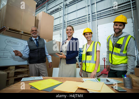 Warehouse workers and managers standing together in warehouse - Stock Image