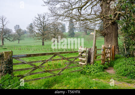 A wooden gate in a fence with access to a signposted public footpath through the Shropshire countryside at Worfield in Shropshire, UK - Stock Image