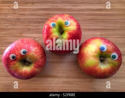 Creative healthy fun food concept. Three Pink Lady apples with googly eyes on a bamboo board with copy space - Stock Image