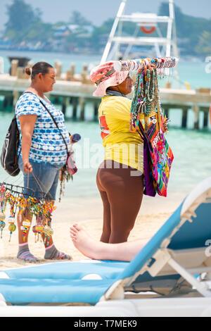 Vendors selling souvenirs to tourists at West Bay Beach Roatan Honduras. - Stock Image