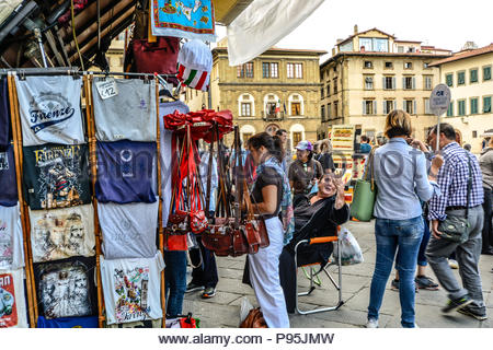 A street vendor selling souvenirs gestures to a tour guide on the Piazza Santa Croce as a customer looks through items for sale in Florence, Italy - Stock Image