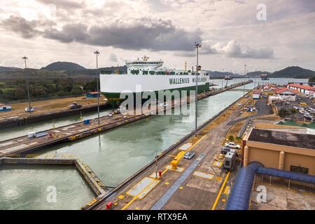 Large transatlantic cargo ship crossing from Atlantic to Pacific Ocean, entering Miraflores Locks in Panama Canal - Stock Image
