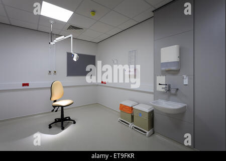 single unoccupied chair in examination room with examination light without people - Stock Image
