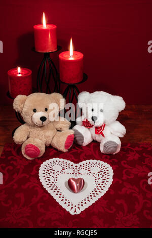 Heart shapped dollie and gemstone, three red candles in metal holders and red rose, two teddy bears on wooden table. - Stock Image