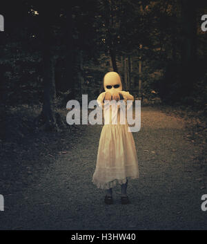 A scary evil ghost girl wearing a white dress and face is walking in the dark woods with her hands up. Use it for - Stock Image