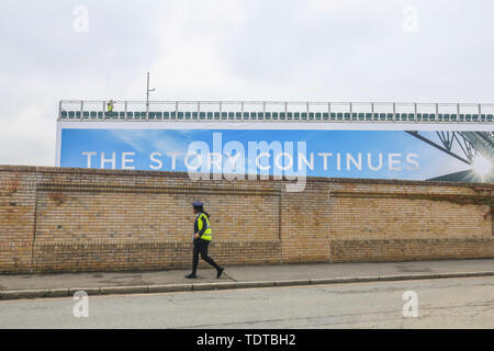 Wimbledon London, UK. 19th June, 2019. A security guard wearing a Hi Vis jacket walks past a spectator stand  as the  (AELTC) All England Lawn Tennis Club prepares to host  r the 2019 Wimbledon Championships Credit: amer ghazzal/Alamy Live News - Stock Image