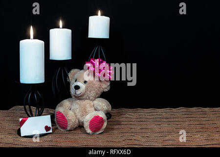 Cudlely teddy bear with pink bow on head, white candles perched on black candle holders on mesh place mat and wooden table with card and dark backgrou - Stock Image