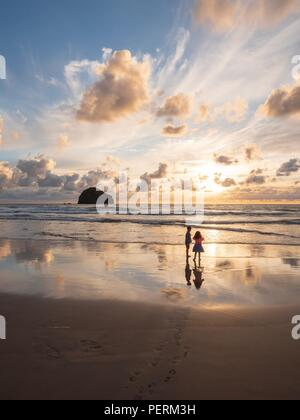Two children stood together on a beach at sunset with the reflection of the sky in the wet sand - Stock Image