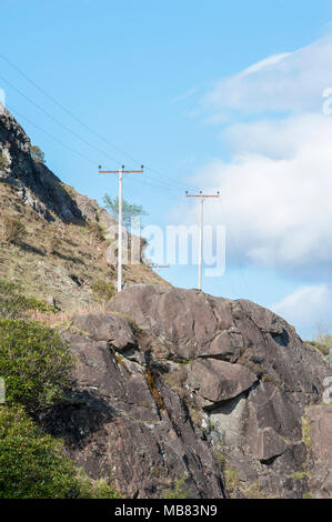 power cables on wooden pylons wodden poles running though mountains - Stock Image