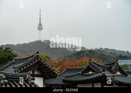 A view of Namsan Tower partly obscured by clouds see over the rooftops of houses at Namsangol Hanok Village, Seoul, South Korea - Stock Image