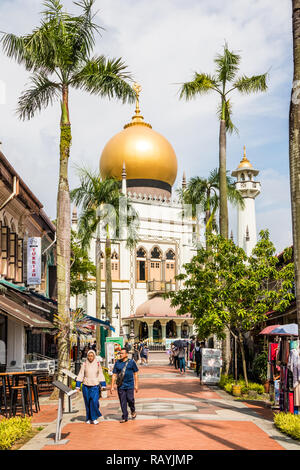 Singapore - 22nd December 2018: Tourists on Arab Street with the Sultan mosque in the background.  This is in the Kampong Glam area - Stock Image