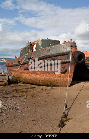 Rusted vessel on the foreshore - Stock Image