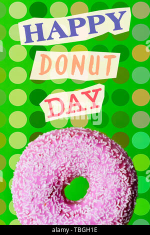 text happy donut day, as magazine cutouts, and a donut, coated with a pink frosting and white sprinkles, on a green background, patterned with dots of - Stock Image