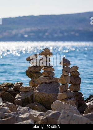 Stack of rocks on beach against bright light - Stock Image