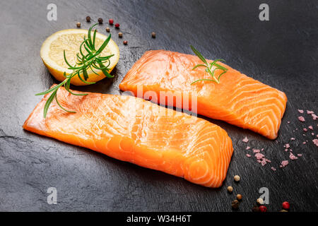Raw salmon with spices on a black background. Two slices of fresh fish with lemon, rosemary, salt, and pepper - Stock Image