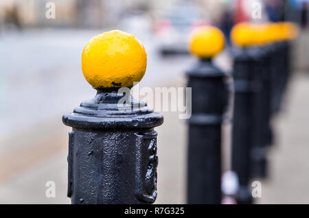 yellow metal ball on street post, blurred city street in the background, Warsaw Poland - Stock Image