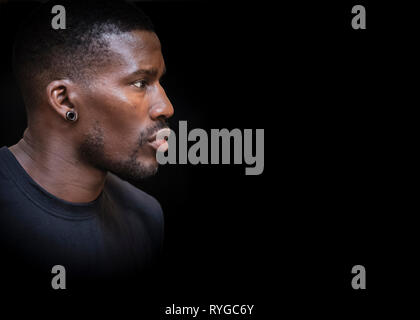 Young handsome black African British man in profile, with short beard and earring against a black background. - Stock Image