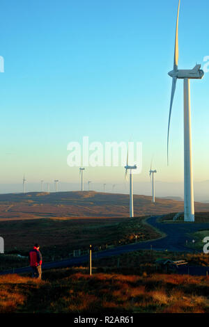 Scotland, UK. 18th Nov 2018. Scotland, UK. 18th Nov 2018. Man strolling through Kelburn Wind Farm, near Largs, in evening light as temperatures start dipping after a beautiful sunny winters day. Credit: PictureScotland/Alamy Live News Credit: PictureScotland/Alamy Live News - Stock Image