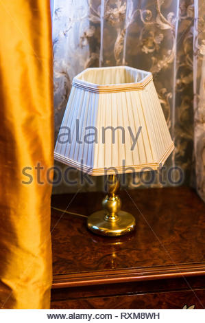 Classic lamp with golden holder standing on a wooden table. - Stock Image