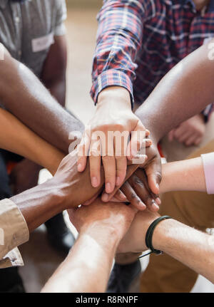 Men joining hands in group therapy - Stock Image
