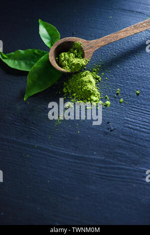 Matcha tea powder in wooden spoon with tea leaves on a dark background with copy space - Stock Image