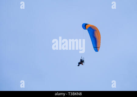 A motorised paraglider against a blue sky. - Stock Image
